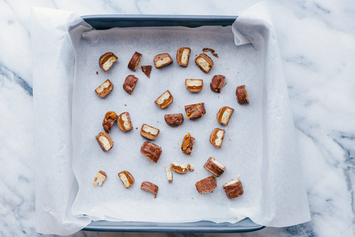 twix candy cut into small piece and placed in 8x8 pan on top of parchment paper to make candy bar fudge.