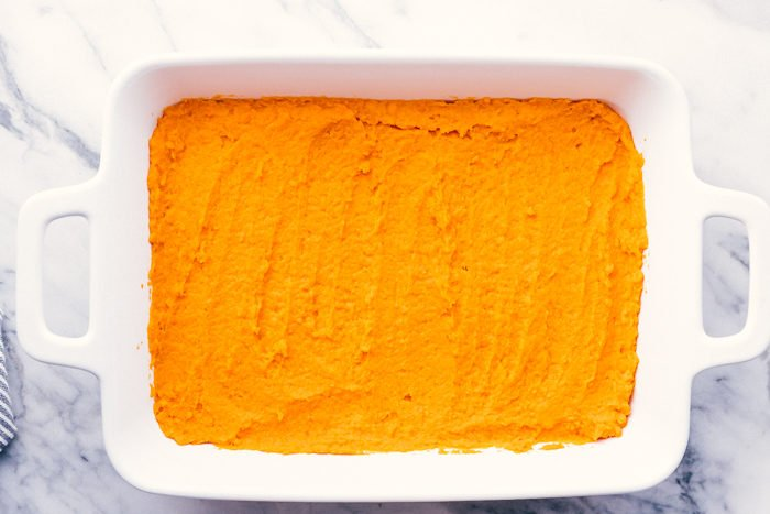 mashed sweet potatoes in a white casserole dish for sweet potato casserole