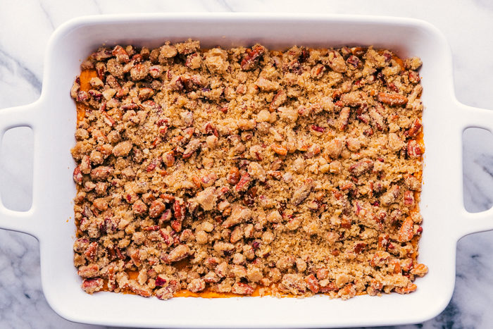 Pecan topping on top of sweet potatoes for sweet potato casserole in a white casserole dish.