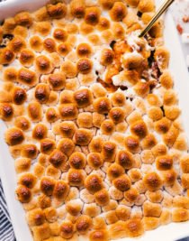 sweet potato casserole in a white casserole dish be served with gold spoon.