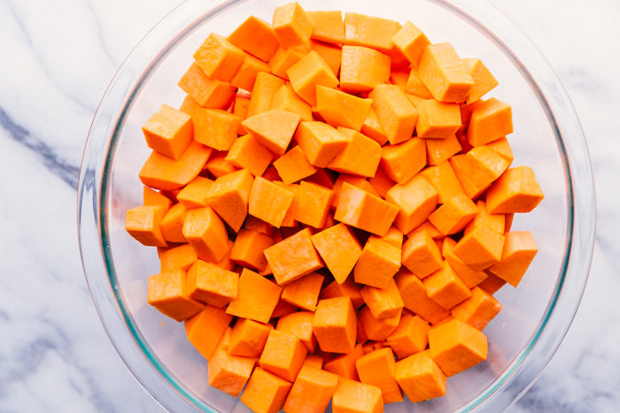 sweet potatoes for sweet potato casserole peeled and cut in a clear bowl.