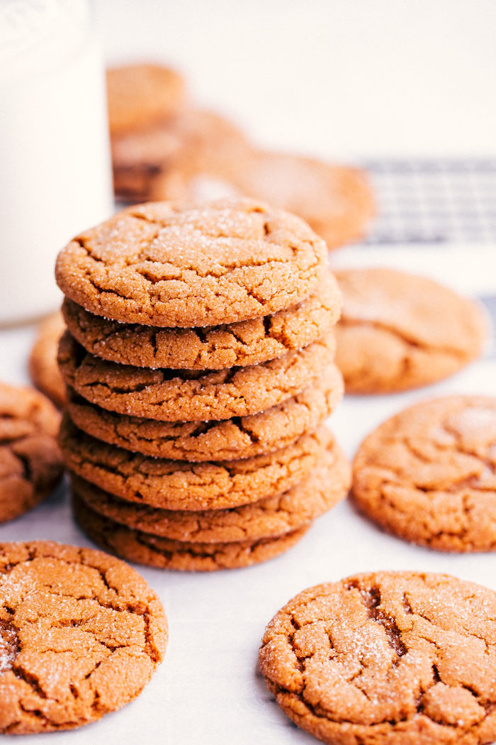 chewy ginger cookies stacked up on cooling rack being served with milk.