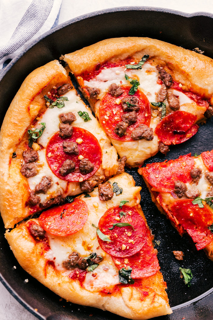 cast iron skillet pizza topped with sausage and pepperoni cut into slices.