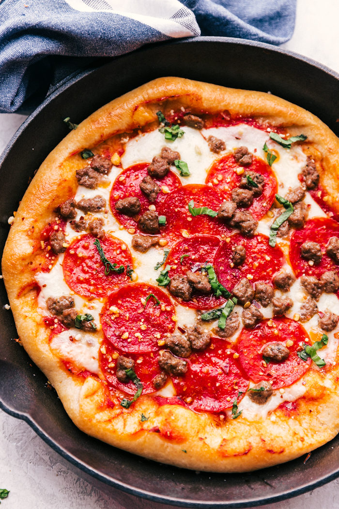 cast iron skillet pizza with cooked with sausage and pepperoni, garnished with fresh basil and red pepper flakes.