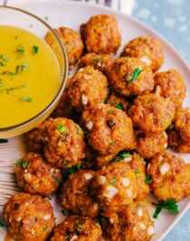spicy sausage cheese balls being served on a white plate with cheese sauce.