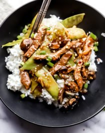 beef stir fry with snow peas served in a black bowl over white rice with a pair of silver chop sticks for contrast.