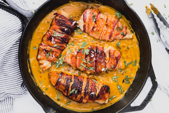 bacon wrapped chicken made in a skillet with chili cheese sauce-perfect keto recipe.