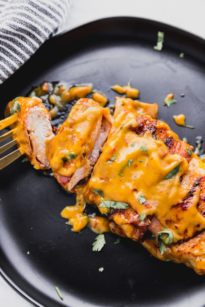 Bacon wrapped chicken with chili cheese sauce on top sliced into pieces on a black plate with gold fork.