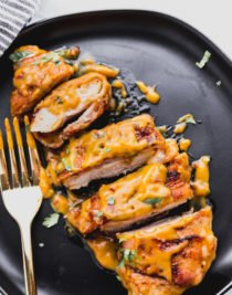 bacon wrapped chicken in chili cheese sauce sliced into pieces on a black plate with gold fork.