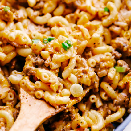 cheeseburger macaroni in a large skillet with a wooden spoon serving pasta.