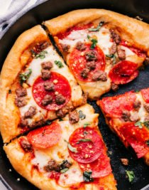 sausage and pepperoni pizza sliced into pieces in a cast iron skillet.