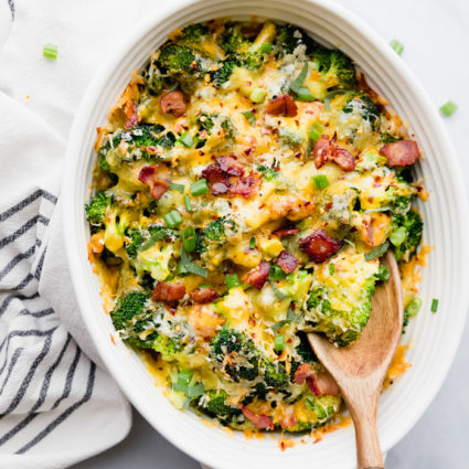 Broccoli cheese casserole in a white casserole dish with wooden spoon to serve sitting on a light background to highlight the colors of the casserole, by The Food Cafe