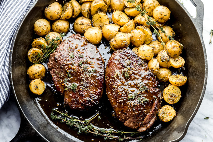 Easy Pan seared Top sirloin steak cooked in a bourbon sauce served with a side of baby potatoes in a cast iron skillet and topped with chopped rosemary-done in 15 minutes, by The Food Cafe