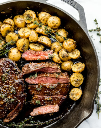 Pan seared top sirloin sliced in a cast iron skillet served along side baby roasted potatoes with bourbon sauce over the top, by The Food Cafe.