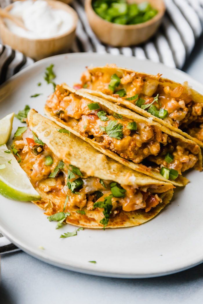 Three baked chicken tacos on a white plate served with sour cream and diced jalapeños on the side and garnished with cilantro by The Food Cafe.