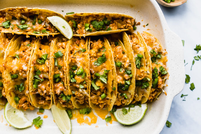 baked chicken tacos by the food cafe loaded with refried beans, chicken, cheese and topped with diced green onions and cilantro , in a white casserole dish garnished with sliced limes, perfect family meal.