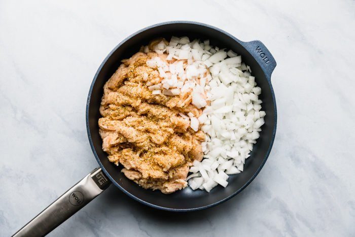 A large skillet with ground chicken and onions on a white background ready to be made for baked chicken tacos, by The Food Cafe