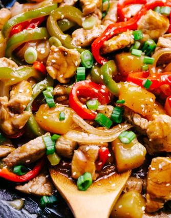 sweet and sour pork with pineapple made in a dark wok with green pepper, red pepper, and onions by The Food Cafe.