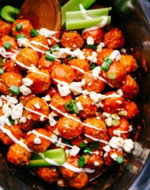 buffalo chicken meatballs in a black slow cooker garnished with diced green onions, blue cheese crumbles, and blue cheese dressing, by the food cafe.