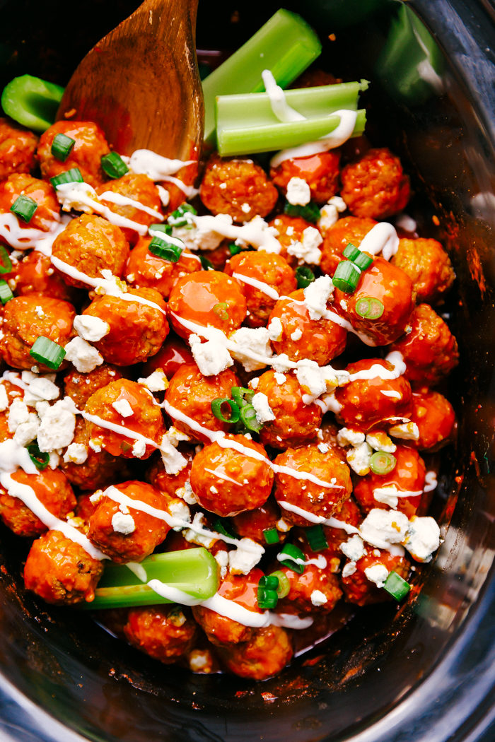Buffalo chicken meatballs made in a black slow cooker garnished with diced green onins, blue cheese crumbles and drizzled with blue cheese dressing with a few pieces of celery for color. A wooden spoon is placed in the slow cooker to use for serving, the perfect super bowl appetizer by The Food Cafe.