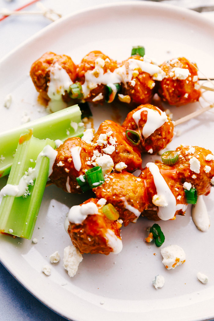 Buffalo chicken meatballs stacked on cocktail toothpicks on a white plate garnished with blue cheese crumbles, diced green onions, and blue cheese dressing by The Food Cafe.