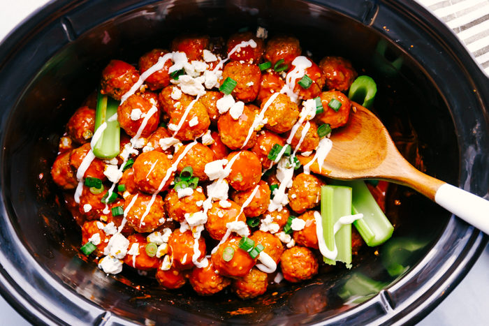 Buffalo chicken meatballs in a black crockpot topped with blue cheese crumbles, blue cheese dressing and green onions with a wooden spoon for serving, by The Food Cafe.
