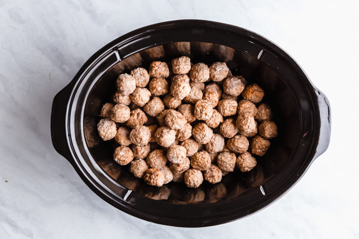 Frozen pre-cooked buffalo meatballs in a black slow cooker on a white background showing how to make buffalo chicken meatballs step by step by The Food Cafe.