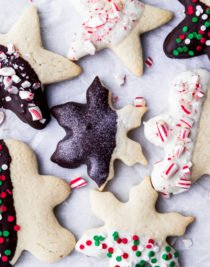 sugar cookies dipped in chocolate decorated with candy toppings and sprinkles laying on a piece of white parchment paper by The Food Cafe