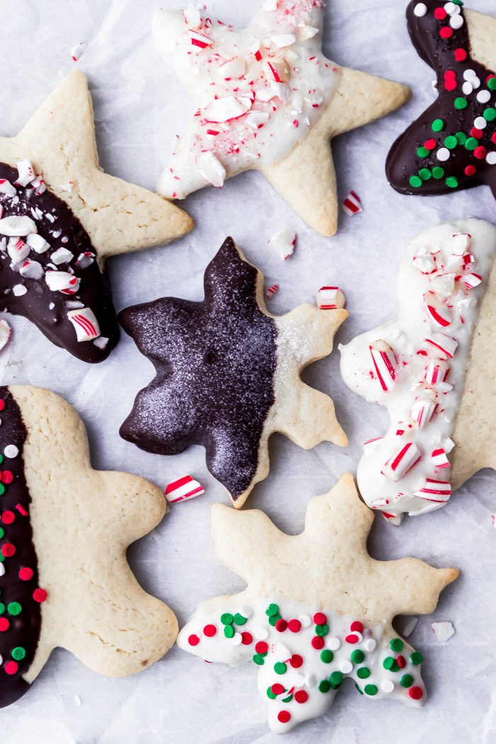Decorated sugar cookies with dark chocolate and white chocolate topped with sprinkles and crushes candy canes on a piece of white parchment paper, by The Food Cafe.