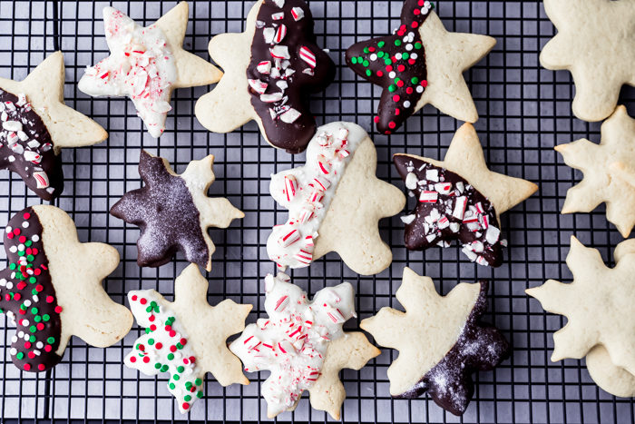 Decorated sugar cookies that have been dipped in dark and white chocolate laid out on a black cookie rack, by The Food Cafe.