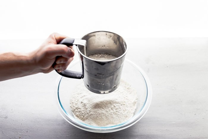 Sifting flout using a flour sifter into a clear bowl to make sugar cookies, by The Food Cafe.