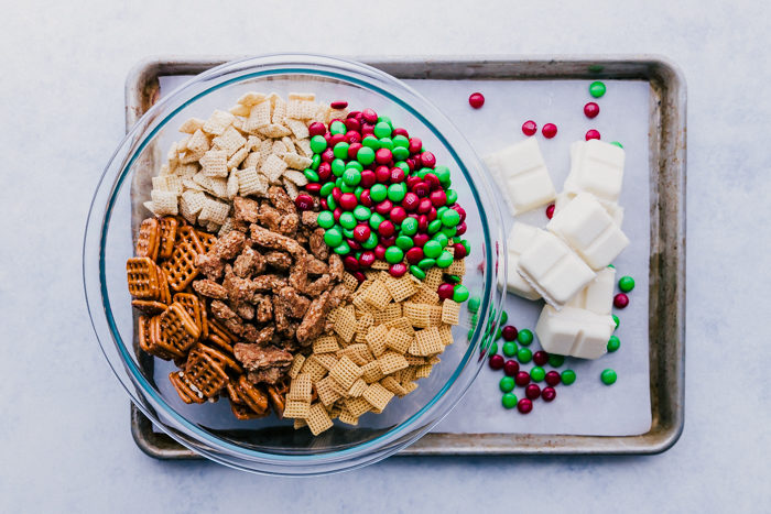 A clear bowl filled with pretzels, chex cereals, granola chunks, and red and green m&ms sitting on a rimmed baking sheet with chunks of white chocolate ready to make white chocolate Chex mix with m&ms by The Food Cafe.