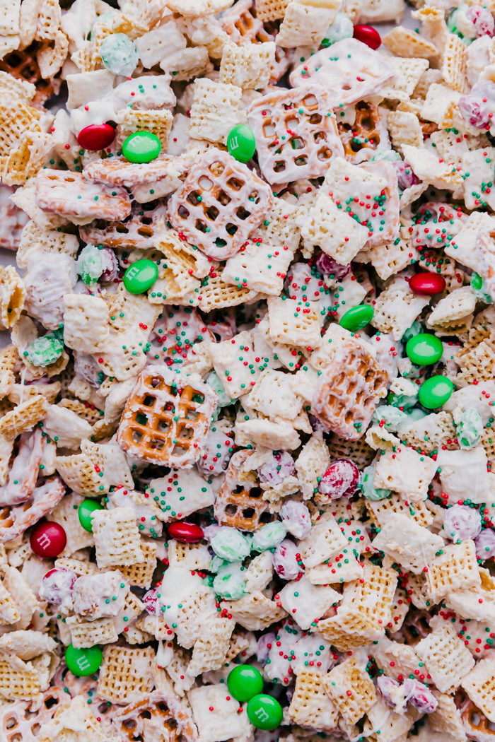 Close up image of all the chocolate coated ingredients in white chocolate Chex mix, perfect for all your Holiday snacking, by The Food Cafe.