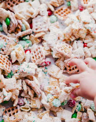 white chocolate chex mix on a rimmed sheet pan with a little girls hand taking a piece off the pan, by The Food Cafe