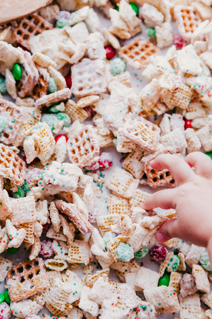 White chocolate chex mix with m&ms on a rimmed baking sheet with a little girls hand taking a piece off the tray, by The Food Cafe.