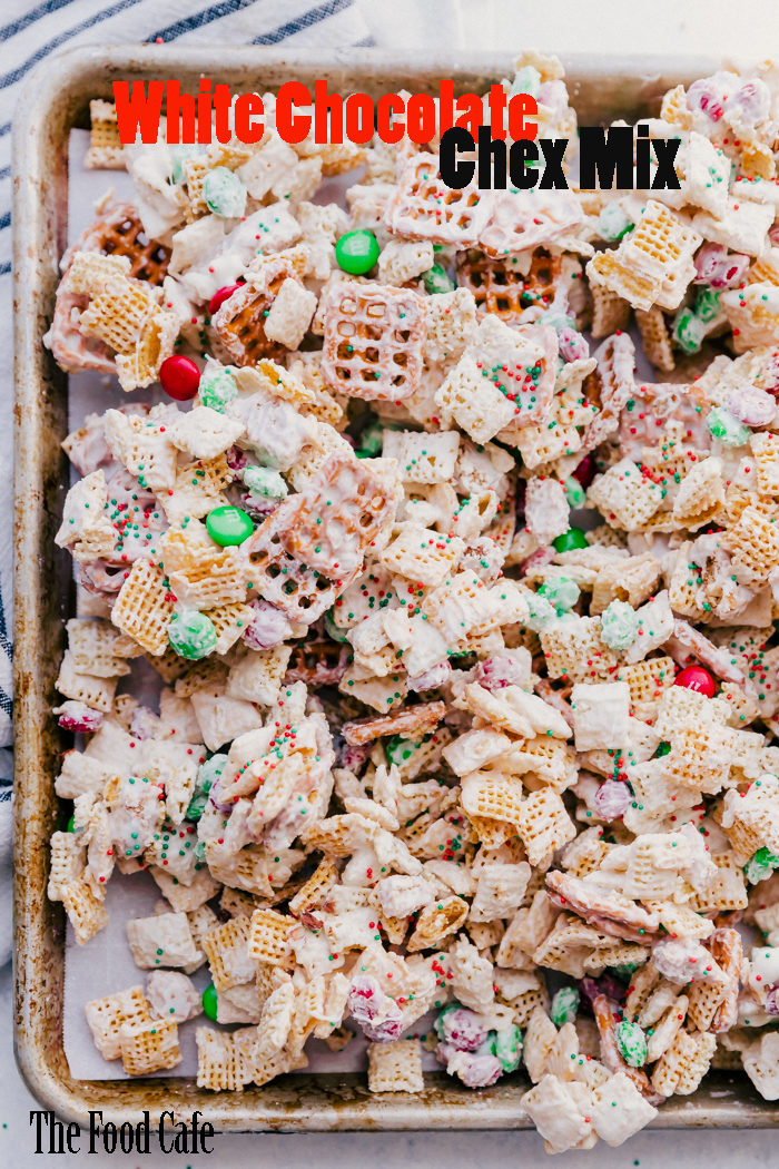 White chocolate chex mix on a rimmed sheet pan by The Food Cafe