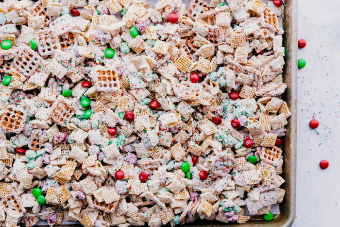 White chocolate chex mix on a rimmed sheet pan loaded with chex, pretzels, granola chunks, M&M's and sprinkles by The Food Cafe.