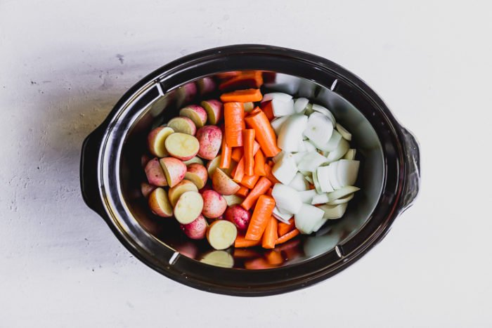 Sliced potatoes, carrots, and onions in a black slow cooker ready for beef stew, by The Food Cafe