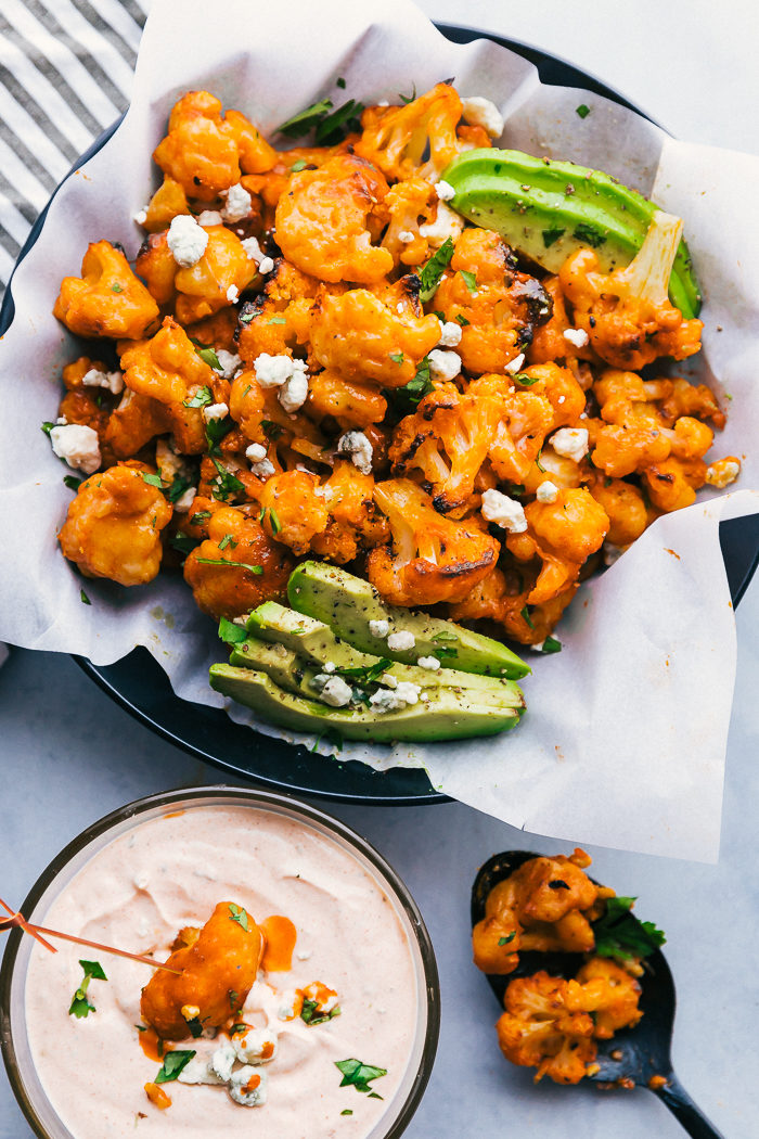 Buffalo cauliflower bites in a black bowl lined with parchment paper and garnished with blue cheese crumbles, chopped parsley, sliced avocado, and a clear bowl with buffalo ranch dip with a piece of buffalo cauliflower dipped in it, by The Food Cafe.
