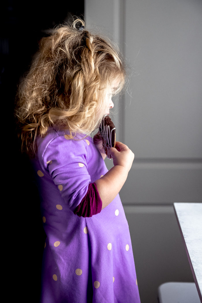 A little girl in a purple dress with blond curly hair standing on a stool eating a chocolate dipped cookie, by The Food Cafe.