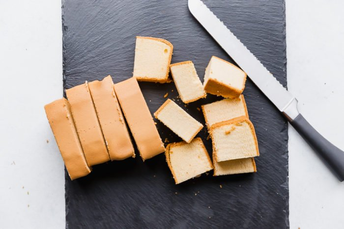 A black cutting board and bread knife used to slice pound cake in 1-inch slices and then cut into small pieces for chocolate dipped cake pops, by The Food Cafe