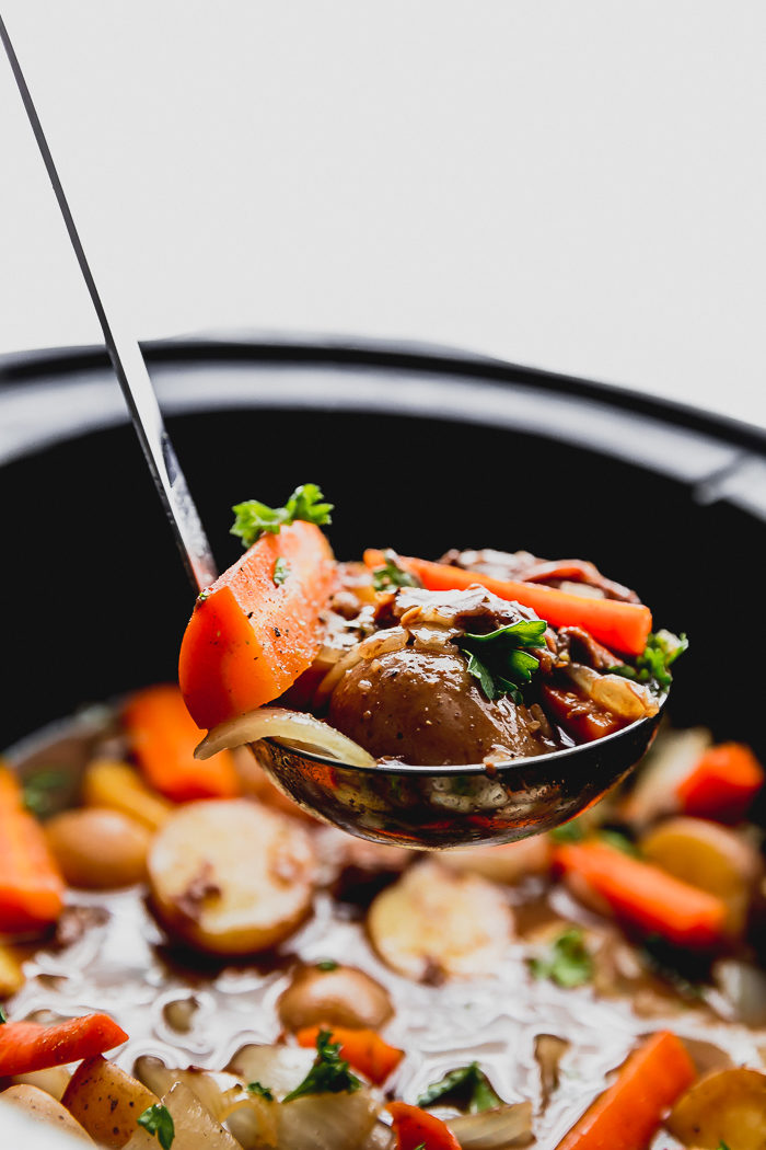 beef stew being ladled out of a black slow cooker with a silver ladle full of carrots, beef, onions, potatoes and garnished with fresh chopped parsley by The Food Cafe.