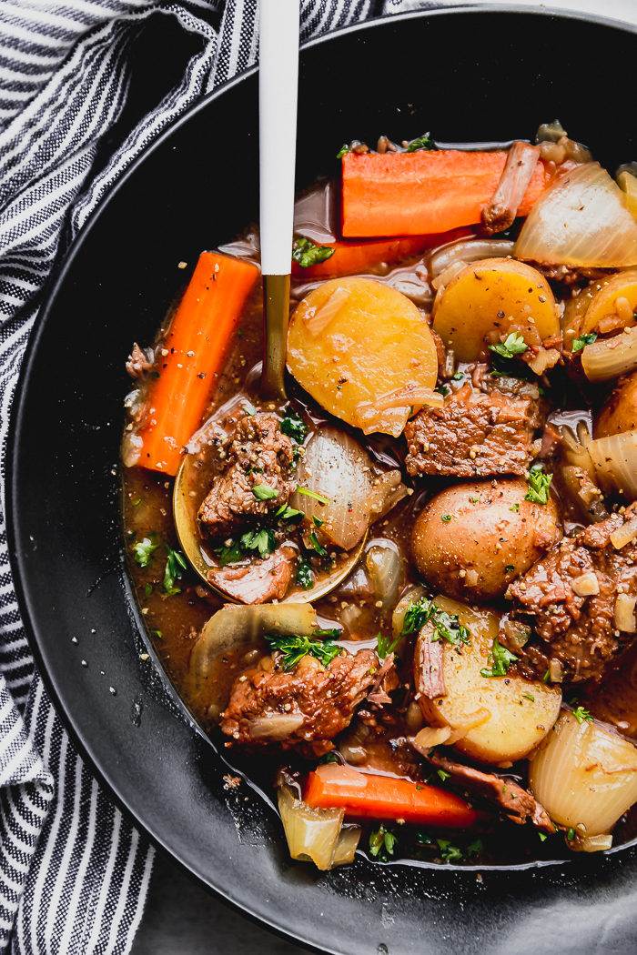 Easy beef stew with carrots, potatoes, onions, and beef made in the slow cooker dished into a black bowl served with a gold spoon with white handle, by the food cafe.