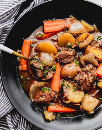 Best ever beef stew served in a black bowl with gold spoon with beef tips, red potatoes, diced carrots and onions by the food cafe.