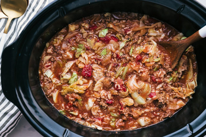 Cabbage roll soup made in a black crockpot with a wooden serving spoon placed in the crockpot for serving on a white background by The Food Cafe