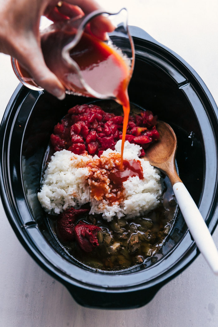 Adding in the vegetable juice to the crockpot cabbage roll soup in a black crockpot with a wooden spoon with white handle to mix by The Food Cafe.