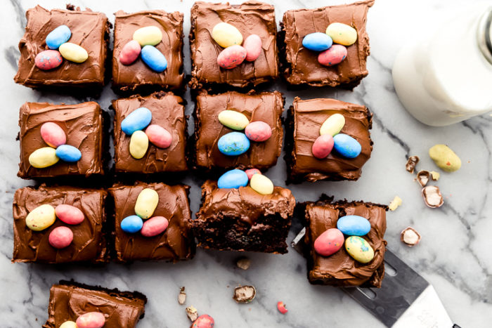 Chocolate Easter Brownies decorated with hard candy chocolate easter eggs, cut into squares on a white marble background with a spatula removing one of the brownies along side a class of milk, by The Food Cafe.