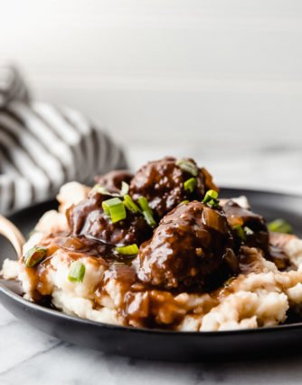 baked meatballs on a bed of mashed potatoes served on a black plate with a gold spoon and a white background, by The Food Cafe.