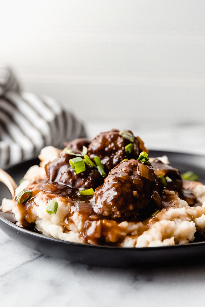 Baked meatballs on a bed of creamy mashed potatoes, served on a black plate sitting on a white background topped with diced chives, by The Food Cafe.