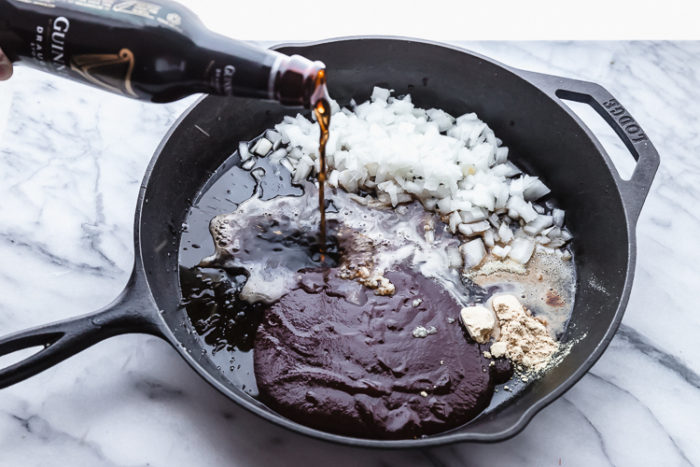 A large black cast iron skillet with diced onion, bbq sauce, dry mustard, molasses, honey, and garlic salt in it. Along with pouring Guinness beer into the skillet to make sauce for baked meatballs, by The Food Cafe.